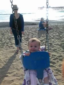 My daughter and me at the beach. She loves the swings. (Not sure who that lady is in the background.)